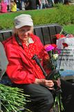 Portrait of a war veteran woman, she holds carnations and smiles. Royalty Free Stock Photography