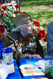 Portrait of a war veteran woman sitting at table. Stock Images