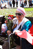 Portrait of a war veteran woman smiling holding flowers buds. Stock Images