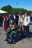 Portrait of a war veteran. Young people pose with him for photos. Stock Photos