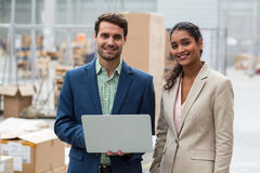 Portrait of warehouse managers standing with the laptop. In warehouse Stock Images