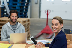 Portrait of warehouse managers using digital tablet and laptop. Portrait of warehouse managers using digital tablet laptop in warehouse Royalty Free Stock Photos