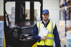 Portrait of warehouse worker with clipboard. In warehouse Royalty Free Stock Photo