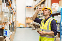 Portrait of warehouse worker with clipboard. In a large warehouse Stock Photo