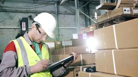 Portrait warehouse worker in protective gear makes notes. Warehouse worker in protective gear makes notes uses a barcode scanner stock footage
