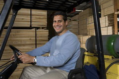 Portrait Of A Warehouse Worker Sitting In Forklift Royalty Free Stock Photography
