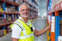 Portrait of warehouse worker standing near shelf Stock Photos
