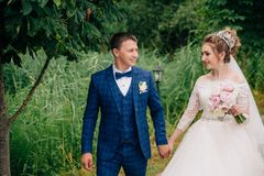 The portrait was just married and walking in the garden. A man looks at his wife lovingly and leads her by the hand. The stock image