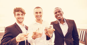 Portrait of well dressed men drinking champagne next to limousine Stock Photo