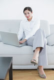 Portrait of a well dressed woman using laptop on sofa Royalty Free Stock Image
