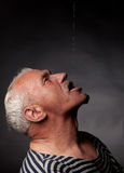 Portrait of a wet man. On whom pours water on a dark background Royalty Free Stock Image