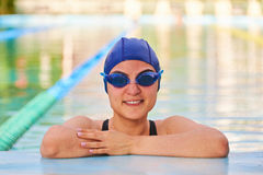 Portrait of wet woman in pool. Background. Swimming woman  in smim goggles and hat Stock Images