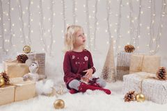 Child girl with blue eyes sitting on floor with toys celebrating Christmas or New Year holiday Royalty Free Stock Images
