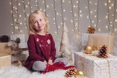 Child girl with blue eyes sitting on floor with toys celebrating Christmas or New Year holiday Royalty Free Stock Photos