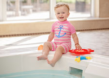 Portrait of white Caucasian baby girl laughing sitting on swimming-pool nosing. Looking in camera, training to swim, healthy active lifestyle Royalty Free Stock Images