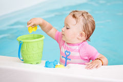 Portrait of white Caucasian baby girl playing with toys in water on swimming pool nosing inside Stock Images