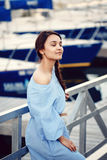 Portrait of white Caucasian brunette woman with tanned skin in blue dress by seashore lakeshore with yachts boats Stock Images