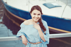 Portrait of white Caucasian brunette woman with tanned skin in blue dress by seashore lakeshore with yachts Stock Image