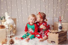 Caucasian children brother and sister in sweaters sitting together hugging celebrating Christmas or New Year