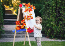 Portrait of white Caucasian toddler child kid boy standing outside in summer autumn park drawing on easel Stock Photos