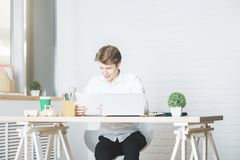 Portrait of white guy in office. Portrait of white guy working on project at modern desk with laptop, paperwork, supplies, coffee cup and other items Royalty Free Stock Photo