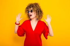Attractive woman with short curly hair. Portrait of a white surprised woman with afrro curly hairstyle in red dress and sunglasses holding her hands up in schock Stock Photos