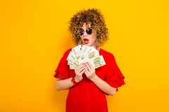 Attractive woman with short curly hair with cash. Portrait of a white surprised woman with afrro hairstyle in red dress and sunglasses holding fan of euro bills Stock Images