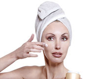 Portrait of the with a white towel on the head putting cosmetic cream on a face on a white background Stock Images