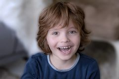 Amsterdam, the Netherlands, 28-4-2018, portrait of a wide smiling boy of seven years, with brown eyes and brown hair and blurred b stock photos