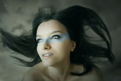 Portrait in the wind. Beautiful fantasy expressive portrait of a girl with long hair in the wind and extravagant makeup in the cloudy sky background Royalty Free Stock Images
