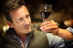 Portrait of winegrower tasting new wine. Winegrower in wine-cellar holding glass of wine Stock Photos