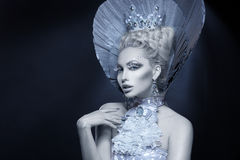 Portrait of winter queen. Portrait of beautiful young woman dressed as winter queen. Creative makeup. Over dark background. Copy space royalty free stock photo