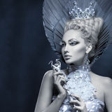 Portrait of winter queen. Portrait of beautiful young woman dressed as winter queen. Creative makeup. Over dark background. Copy space Stock Photo
