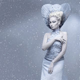 Portrait of winter queen. Portrait of beautiful young woman dressed as winter queen. Creative makeup. Over grey background. Copy space Royalty Free Stock Images