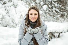 portrait winter woman young Φυσώντας χιόνι χειμερινών γυναικών στο δάσος Στοκ Φωτογραφίες