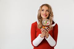 Portrait of a wishful blonde woman. Dressed in red New Year costume standing over white background, holding snowball royalty free stock image