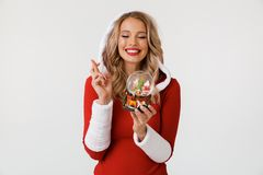 Portrait of a wishful blonde woman. Dressed in red New Year costume standing over white background, holding snowball, fingers crossed stock photos