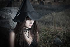 Portrait of the witch. Pretty witch sitting on the stone in the fields Stock Image