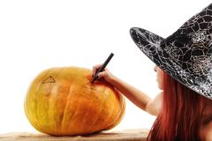 Portrait of a witch with red hair that draws on a pumpkin Royalty Free Stock Images