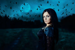 Portrait of a witch. A young witch on background of a full moon and a flock of crows. Portrait of a attractive woman in a black dress in a low key. Fantasy Royalty Free Stock Photography