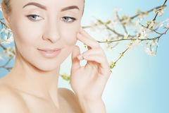 Portrait wom woman with sakura branches on blue background Royalty Free Stock Images