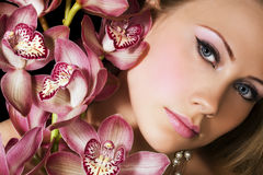Portrait of woman. With pink orchids Royalty Free Stock Photography