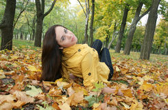 Portrait of a woman. Closeup portrait of a woman lying on ground covered with leaves Royalty Free Stock Image