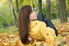 Portrait of a woman. Closeup portrait of a woman lying on ground covered with leaves Royalty Free Stock Photography