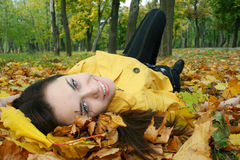 Portrait of a woman. Closeup portrait of a woman lying on ground covered with leaves Stock Image