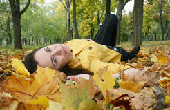 Portrait of a woman. Closeup portrait of a woman lying on ground covered with leaves Stock Photo