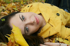 Portrait of a woman. Closeup portrait of a woman lying on ground covered with leaves Royalty Free Stock Photo