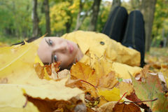 Portrait of a woman. Closeup portrait of a woman lying on ground covered with leaves Stock Photography