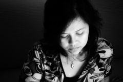 Portrait of a woman. A black and white portrait of an asian woman looking down Stock Image