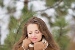 Portrait of woman against fir-tree in winter outdoors. Portrait of relaxed young woman against fir-tree in winter outdoors Royalty Free Stock Images